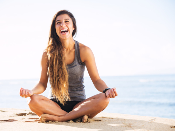 Woman laughing and doing yoga on a beach